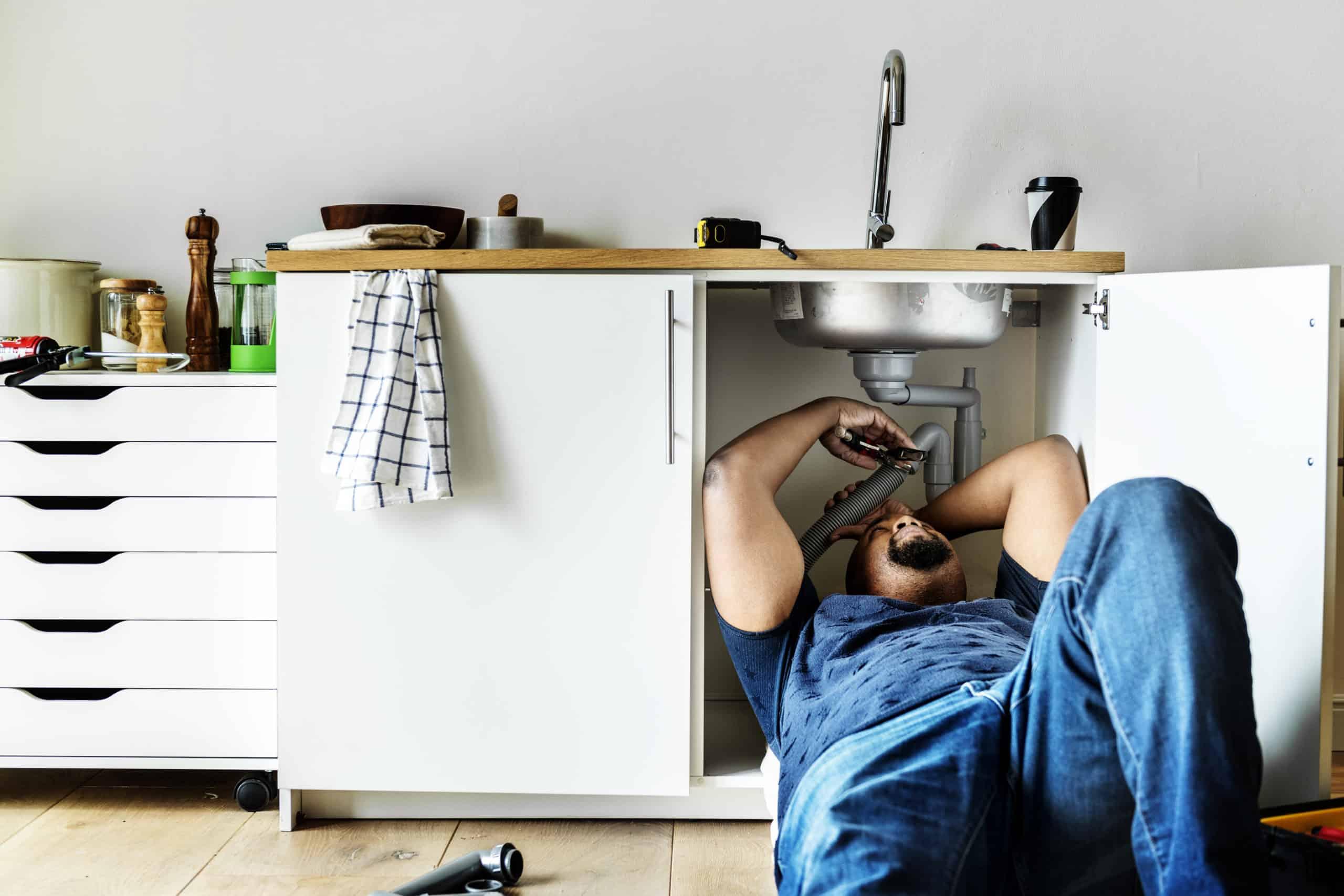 Plumber man fixing kitchen sink